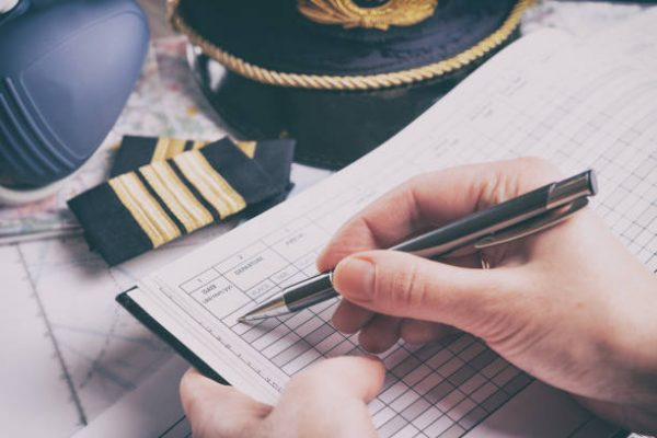 Close up of an airplane pilot hand filling in an pre-fligh checklist and holding weather forecast with equipment including hat, epaulettes and other documents in background